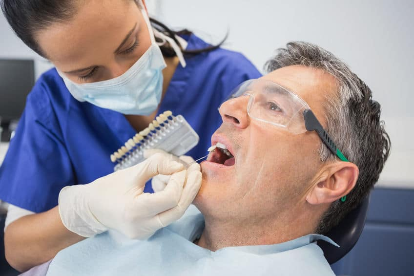 Dentist comparing teeth whitening of her patient in dental clinic